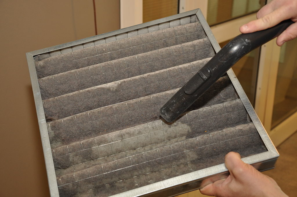 cleaning air filter with vacuum to improve indoor air circulation