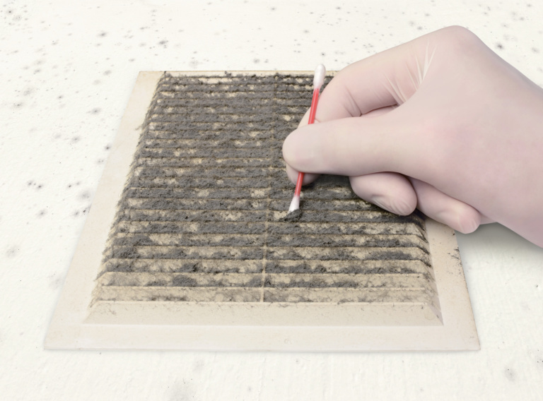 person gloved check ventilation in the dirt with a cotton swab, cleaning dusty ventilation grilles, on a moldy white wall